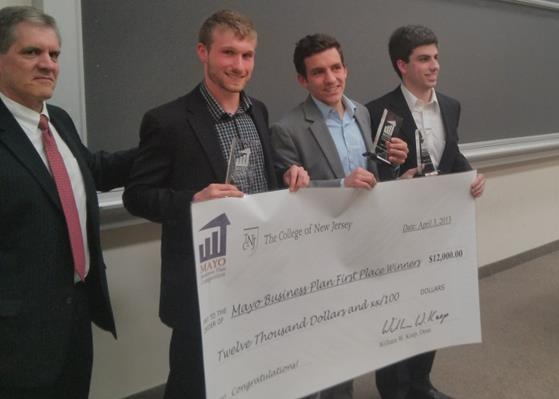 (Left-right) Dean Keep presents the 1st Place prize of $12,000 to M&S Guitars: James Seyffart, Alex Matteson, and Tim Pfenninger. 2nd Place went to Campus Corner Laundry and 3rd Place to SurpriseMe at the Finale on April 3rd. (Photo courtesy of Deric Raymond